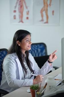 Glimlachende mooie jonge vrouwelijke arts die rapport of medische kaart op het computerscherm leest en aantekeningen maakt in document