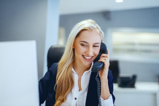 Glimlachende mooie kaukasische onderneemster die telefoongesprek heeft terwijl het zitten in bureau. grote geesten denken onafhankelijk, niet hetzelfde.