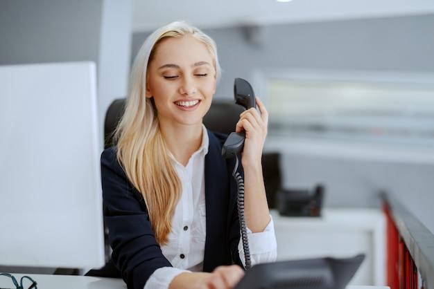 Glimlachende mooie kaukasische onderneemster die telefoongesprek heeft terwijl het zitten in bureau. het leven is verandering. groei is optioneel. kies verstandig.