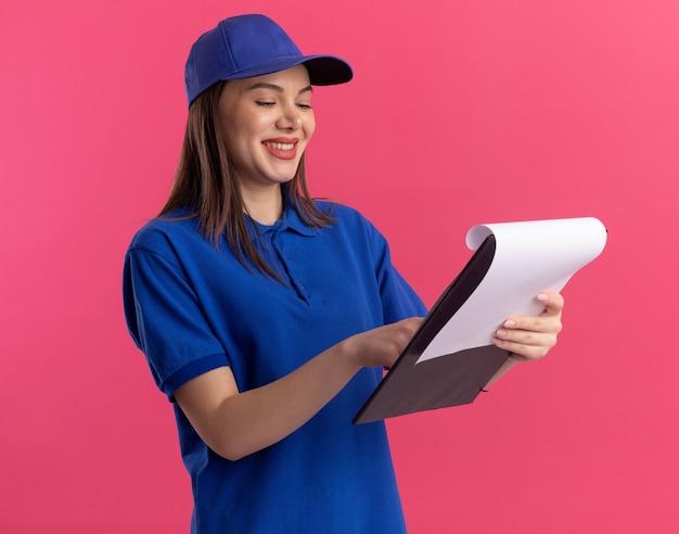 Glimlachende mooie leveringsvrouw in eenvormig bedrijf en kijkend naar klembord dat op roze muur met exemplaarruimte wordt geïsoleerd