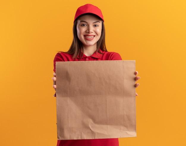 Glimlachende mooie leveringsvrouw in uniform papier pakket op oranje uitrekken