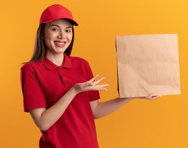 Glimlachende mooie leveringsvrouw in uniforme ruimen en punten op papierpakket op oranje