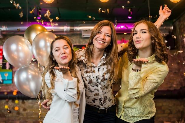 Glimlachende mooie meisjes die en in een nachtclub stellen glimlachen