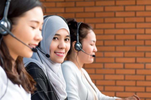 Glimlachende mooie moslimvrouw die in call centre werkt