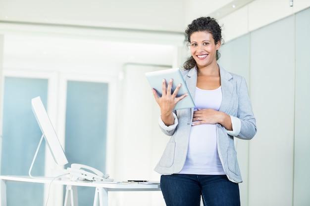 Glimlachende mooie onderneemster die digitale tablet gebruiken