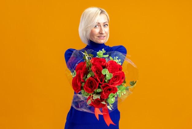 Glimlachende mooie slavische vrouw die op valentijnsdag een boeket bloemen uithoudt, geïsoleerd op een oranje muur met kopieerruimte