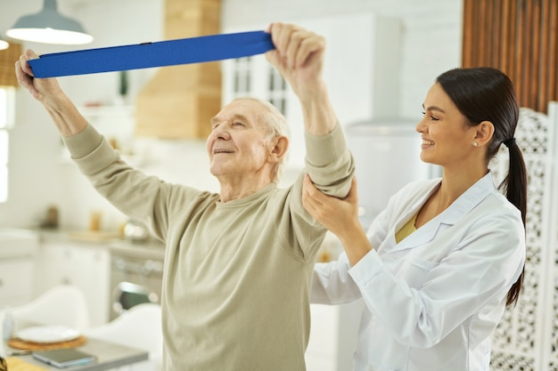 Glimlachende mooie verpleegster die een oudere man helpt om thuis oefeningen te doen