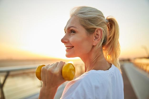 Glimlachende mooie, volwassen blanke vrouwelijke atleet met een halter in haar hand die buiten staat