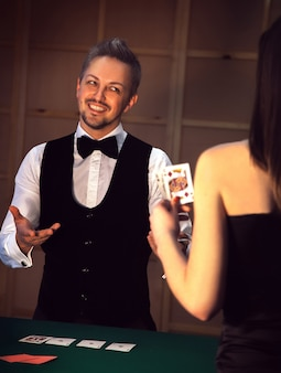 Glimlachende mooie volwassen dealer in een wit overhemd en vlinderdas in het casino. afhankelijk van het concept van gokken en casino's