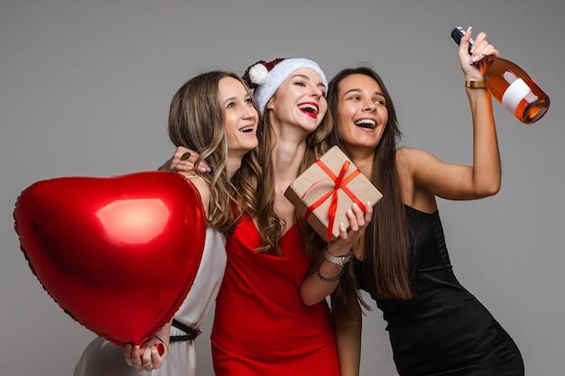 Glimlachende mooie vriendinnen gaan samen vieren terwijl ze een hartvormige ballon en een geschenkdoos, champagne vasthouden.