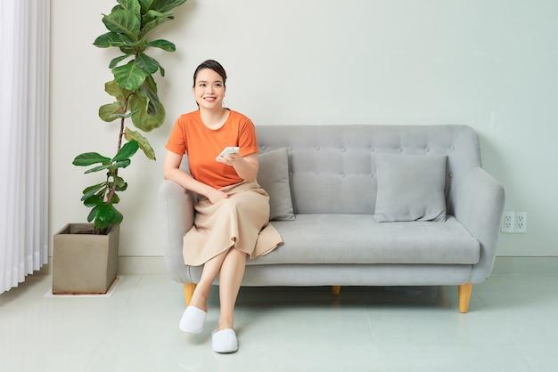 Glimlachende mooie vrouw die de afstandsbediening van de airconditioner gebruikt terwijl ze thuis op de bank zit