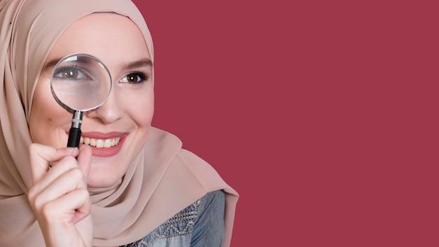 Glimlachende mooie vrouw die door meer magnifier over heldere gekleurde oppervlakte kijkt