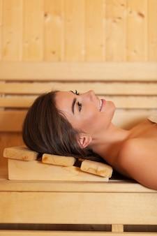 Glimlachende mooie vrouw die in sauna rust