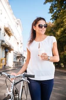 Glimlachende mooie vrouw die in zonnebril met fiets en afhaalkoffie loopt