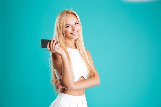 Glimlachende mooie vrouw die mobiele telefoon houdt en voorzijde bekijkt die op de blauwe muur wordt geïsoleerd