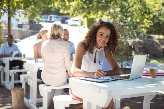Glimlachende mooie vrouw die op klembord in restaurant schrijft
