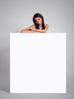 Glimlachende mooie vrouw die op leeg whiteboard leunt