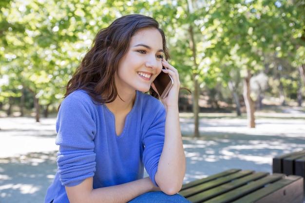 Glimlachende mooie vrouw die op mobiele telefoon in park babbelen