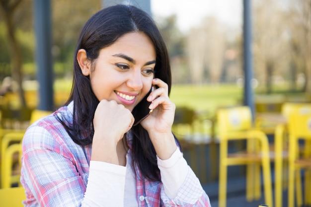 Glimlachende mooie vrouw die op mobiele telefoon in straatkoffie spreekt