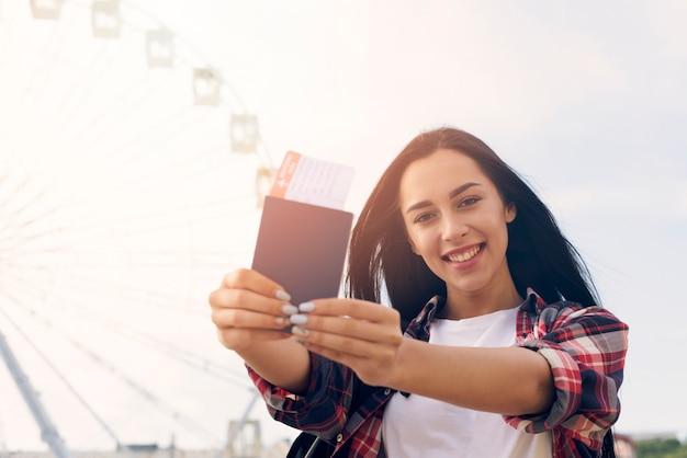 Glimlachende mooie vrouw die paspoort en luchtkaartje tonen die zich dichtbij reuzenrad bevinden