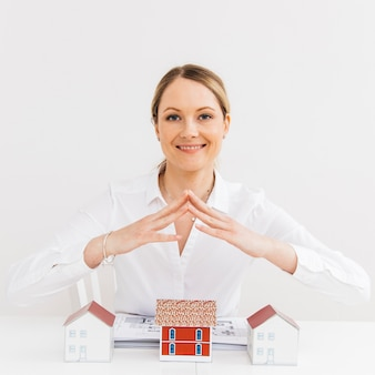 Glimlachende mooie vrouw die veiligheid geeft om huis op werkplaats te modelleren