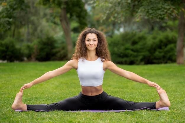 Glimlachende mooie vrouw die yogaoefeningen doet