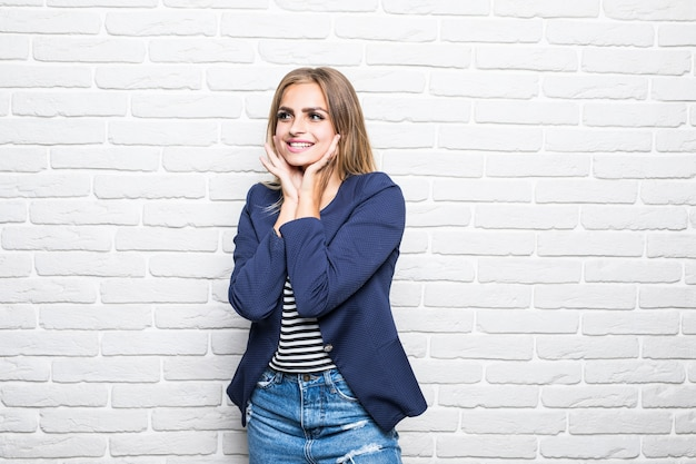 Glimlachende mooie vrouw die zich op witte bakstenen muur op muur bevindt