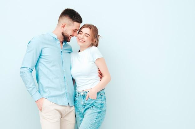 Glimlachende mooie vrouw en haar knappe vriendje. gelukkige vrolijke familie met tedere momenten in de buurt van lichtblauwe muur in studio