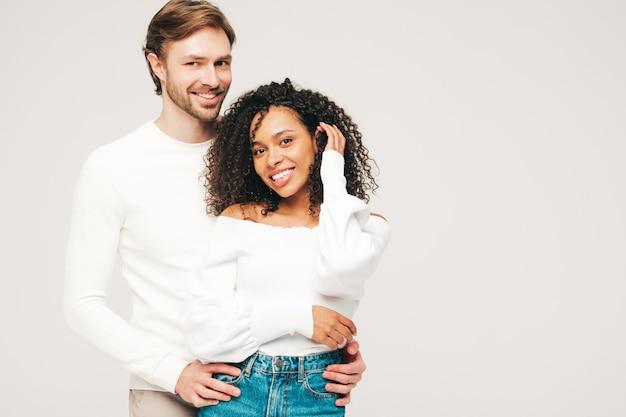 Glimlachende mooie vrouw en haar knappe vriendje. gelukkige vrolijke multiraciale familie met tedere momenten op grijs Gratis Foto