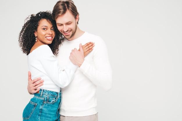 Glimlachende mooie vrouw en haar knappe vriendje. gelukkige vrolijke multiraciale familie met tedere momenten op grijs