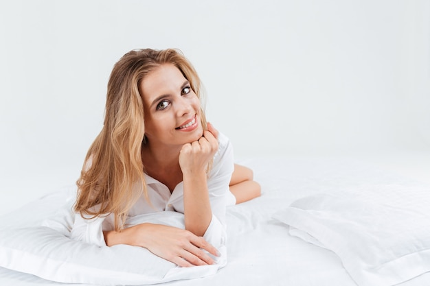 Glimlachende mooie vrouw in wit overhemd die in bed ligt en camera bekijkt