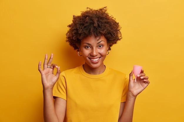 Glimlachende mooie vrouw keurt het gebruik van menstruatiecup goed, maakt goed gebaar en houdt siliconenproduct vast om in de vagina in te brengen, geeft aanbevelingen voor vrouwen beginner cup-gebruikers geïsoleerd op geel