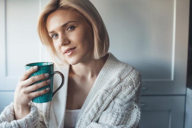 Glimlachende mooie vrouw met blond haar die een kopje thee drinken in de keuken die een gebreide trui draagt