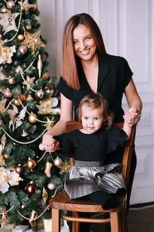 Glimlachende mooie vrouw met haar grappige meisje dichtbij kerstboom