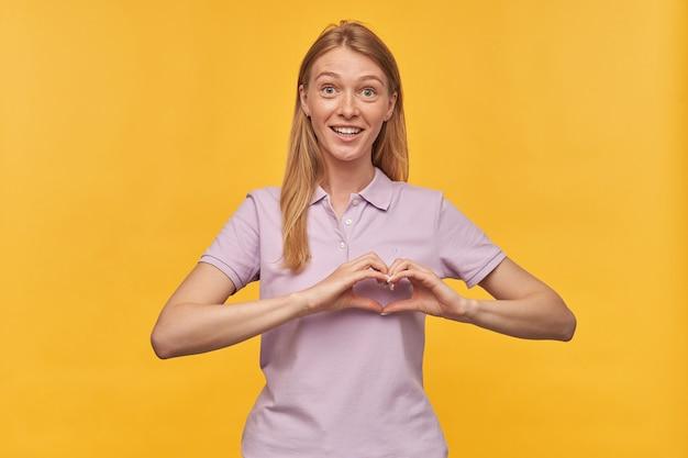 Glimlachende mooie vrouw met sproeten in lavendelt-shirt die hartvorm toont door handen en liefde op geel voelt