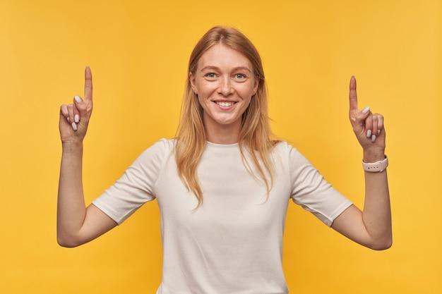 Glimlachende mooie vrouw met sproeten in witte t-shirt staan en naar de lege ruimte met twee vingers op beide handen op geel