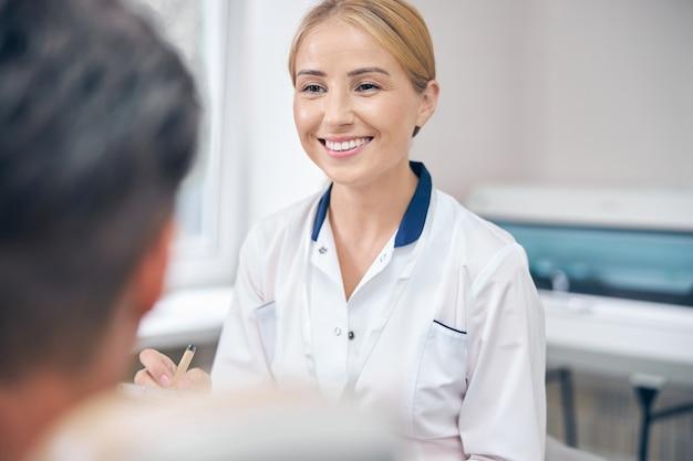 Glimlachende mooie vrouw onderzoekt de patiënt op kantoor en schrijft informatie over gezondheid op het klembord