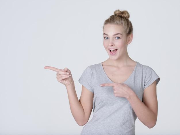 Glimlachende mooie vrouw wijzende vinger weg over grijze achtergrond. kijkend naar de camera