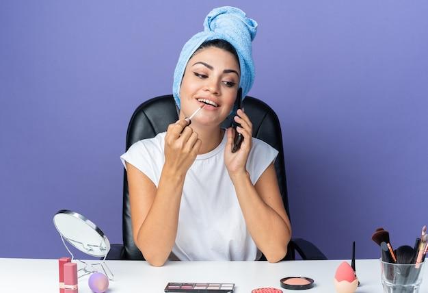 Glimlachende mooie vrouw zit aan tafel met make-uptools gewikkeld haar in een handdoek die lipgloss aanbrengt