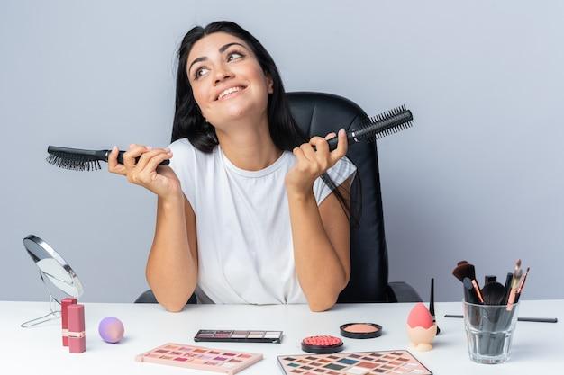 Glimlachende mooie vrouw zit aan tafel met make-uptools met kammen die handen spreiden