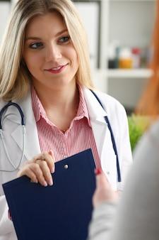 Glimlachende mooie vrouwelijke medicijndokter uitleggen