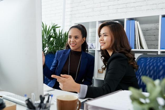 Glimlachende mooie vrouwelijke ondernemers bespreken diagram of presentatie op computerscherm wanneer ha...