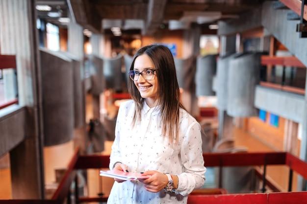 Glimlachende mooie vrouwelijke student met bruin haar en oogglazen die notitieboekje houden, en zich op klasse beginnen te wachten wachten.