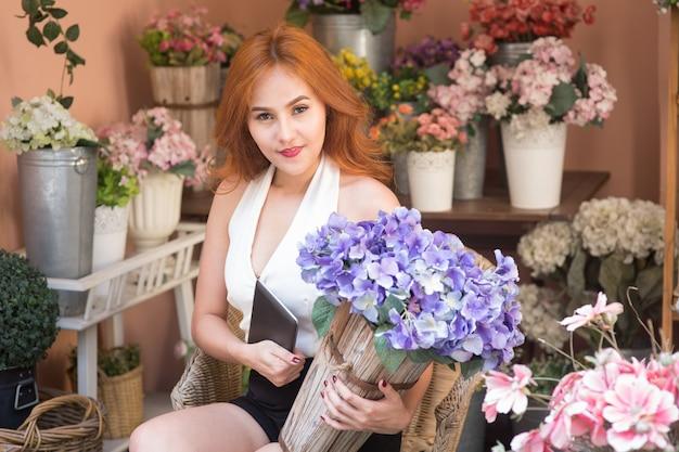 Glimlachende mooie zakenvrouw bij bloemenwinkel met digitale tablet en boeket