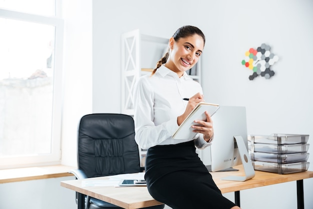 Glimlachende mooie zakenvrouw zittend op het bureau en het maken van aantekeningen