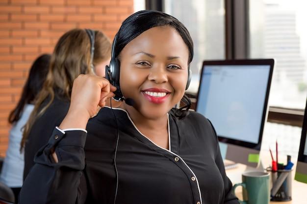 Glimlachende mooie zwarte onderneemster die in call centre werkt