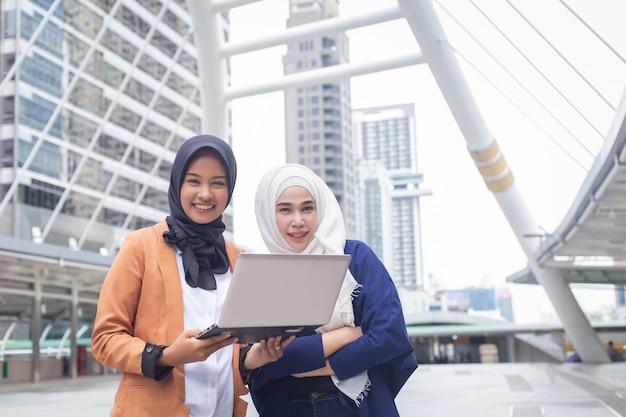 Glimlachende moslimonderneemsters die met laptop computer aan stadsstraat werken.