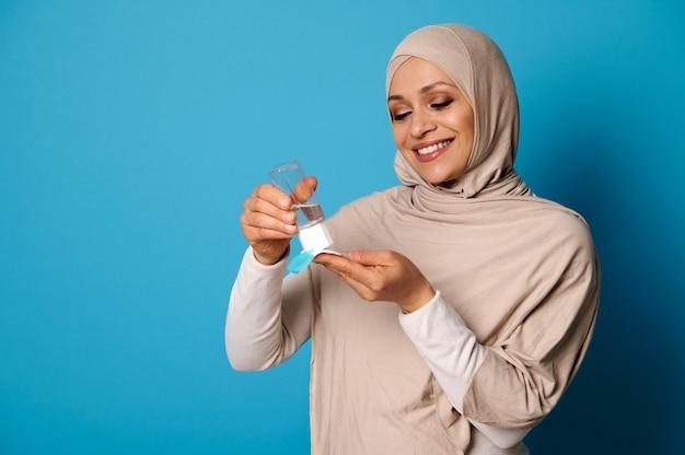Glimlachende moslimvrouw die beige hijab draagt die micellaire make-uplotion op wattenschijfje toepast.