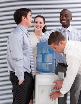 Glimlachende multi-etnische bedrijfsmensen die bij een waterkoeler interactie aangaan