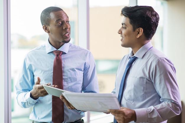Glimlachende multi-etnische bedrijfsmensen die startideeën delen